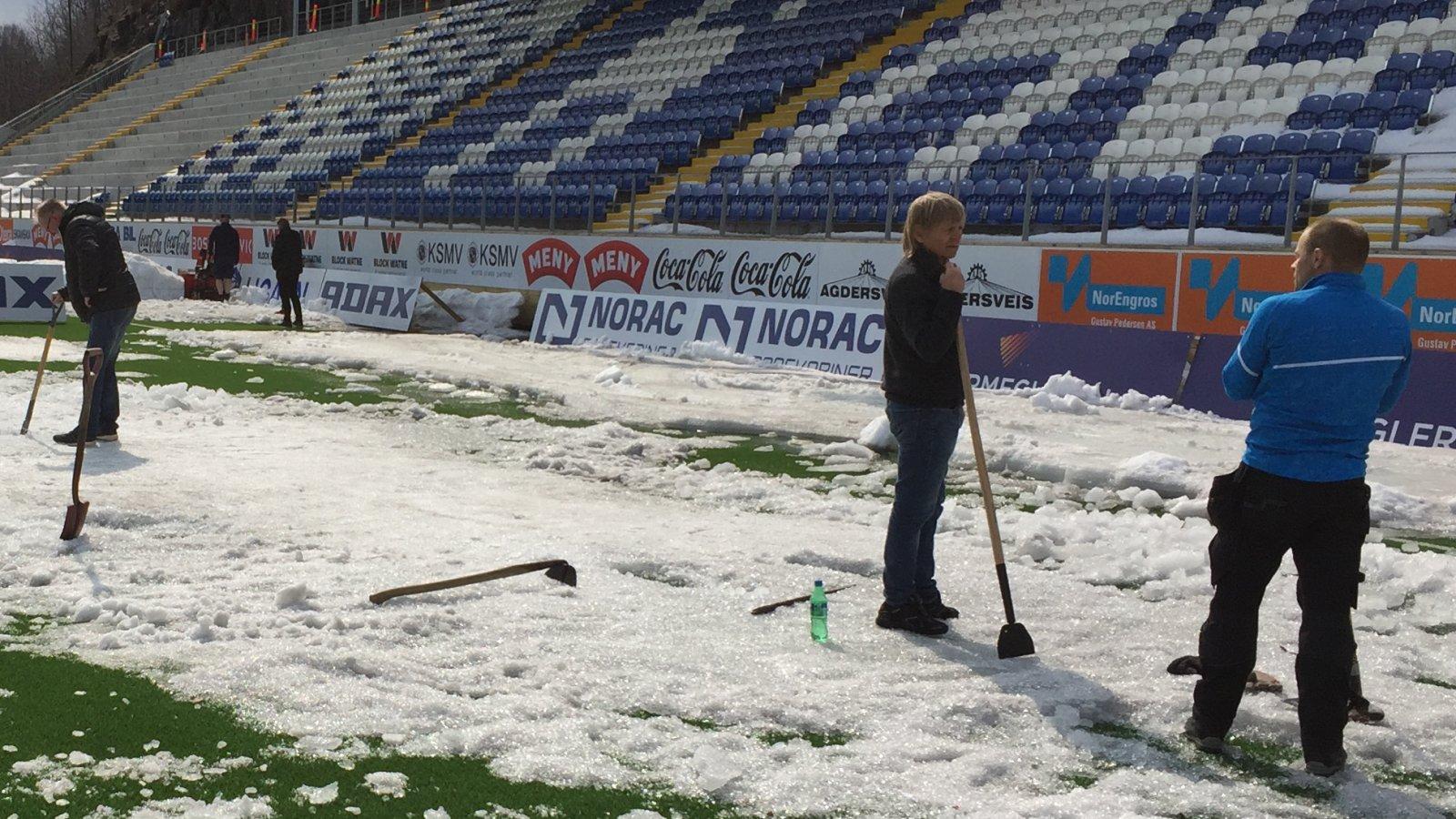 Preben Jørgensen har en pauseprat sammen med Arendal kommunes anleggsansvarlige Helge Hott Johansen lørdag ettermiddag. Først søndag var de ferdige med å fjerne all is og snø på banen.